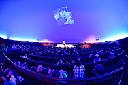 Garden City, New York, USA. June 21, 2018. NASA space shuttle astronaut MIKE MASSIMINO, a Long Island native, is on stage giving free lecture to full house audience in the JetBlue Sky Theater Planetarium at the Cradle of Aviation Museum. Photo projected on planetatium dome wall was taken when Massimino was sending the first ever tweet from space.