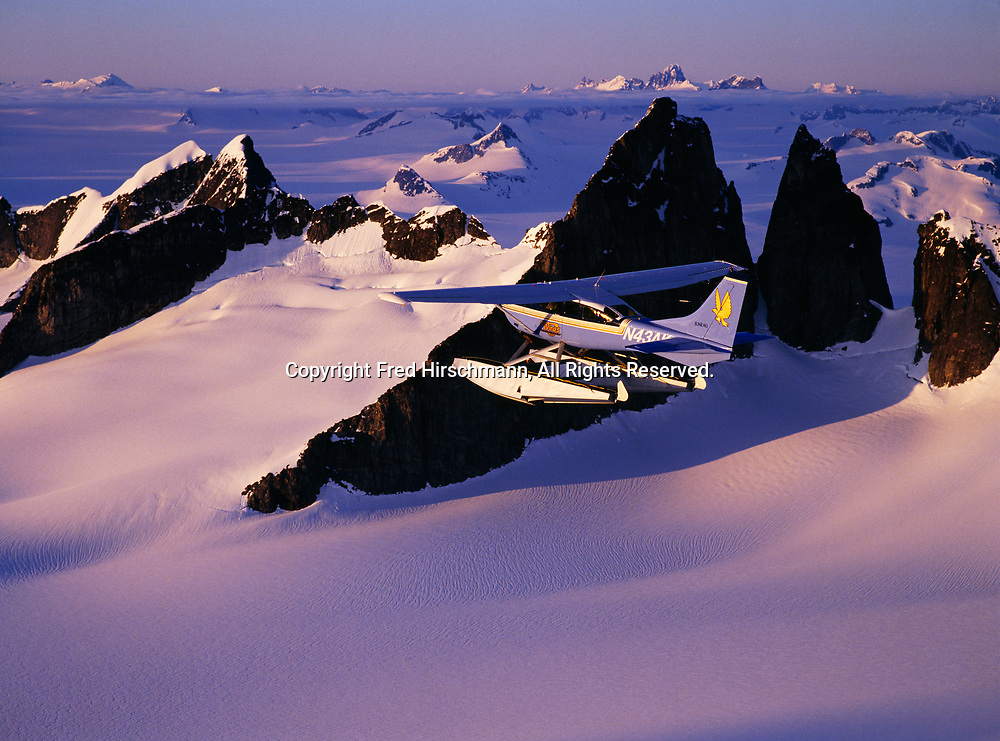 Wings of Alaska Cessna 206 flying over nunataks of the Coast Range rising above the Juneau Icefield, Tongass National Forest, Southeast Alaska.