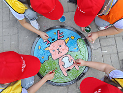 June 13, 2017 - Qinhuangdao, Qinhuangdao, China - Qinhuangdao, CHINA-June 13 2017: (EDITORIAL USE ONLY. CHINA OUT)..Students draw creative paintings on sewer covers in Qinhuangdao, north China's Hebei Province, June 13th, 2017. (Credit Image: © SIPA Asia via ZUMA Wire)