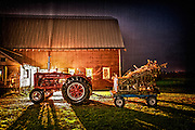 McCormick Tractor pulled up infront of barn in the rain.