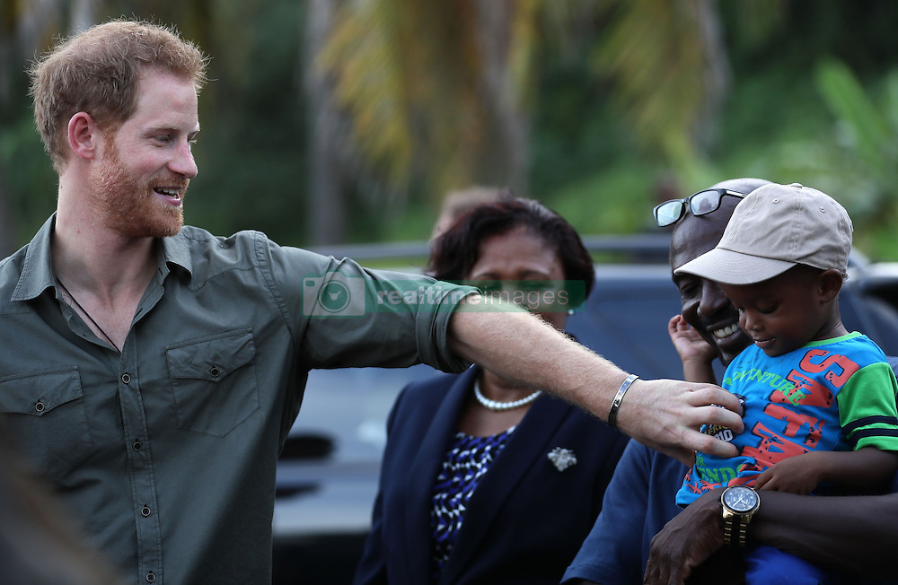 Jyasi Junior Nash, two, is tickled by Prince Harry as he leaves Colonarie Beach, Saint Vincent and the Grenadines, during the second leg of his Caribbean tour.