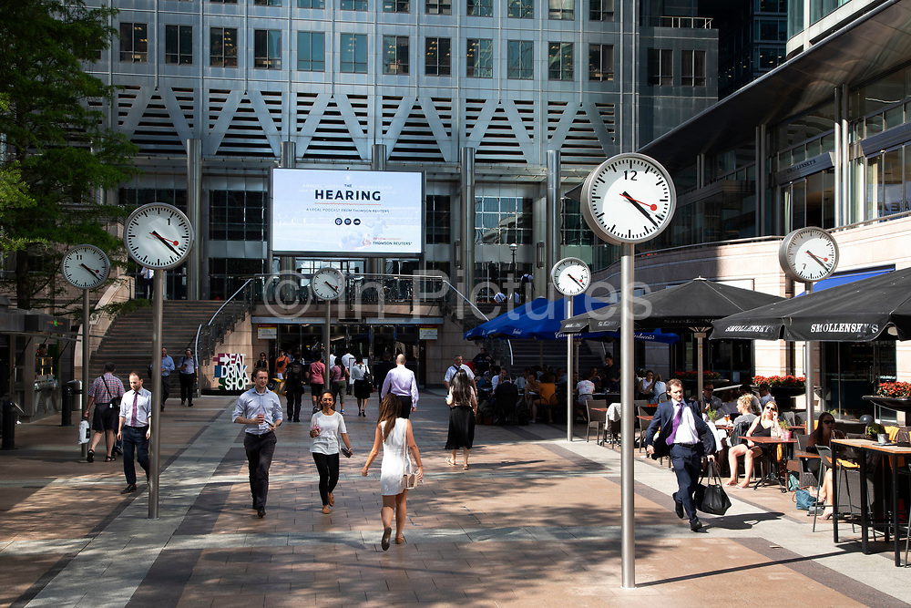 City workers walk under the clocks of Nash Court in Reuters Plaza at the base of One Canada Square in Canary Wharf financial district in London, England, United Kingdom. Canary Wharf is a financial area which is still growing as construction of new skyscrapers continues.