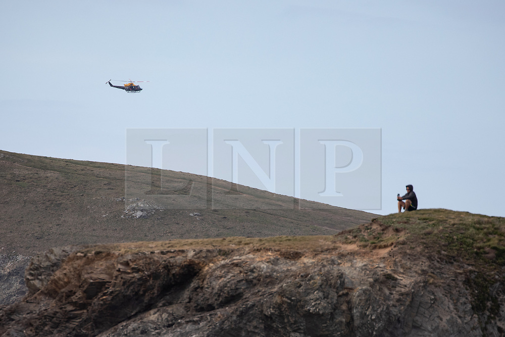 © Licensed to London News Pictures. 07/04/2020. Padstow, UK. A man sits on a rock as a 'Search and Rescue' helicopter flies over Constantine Bay on the north coast of Cornwall this afternoon. The weather in the south-west is forecast to be warm in the coming days. Photo credit : Tom Nicholson/LNP