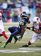 Seattle Seahawks running back Marshawn Lynch (24) twists his body as he runs for a fourth quarter first down as he gets tackled by Arizona Cardinals inside linebacker Kevin Minter (51) during the NFL week 12 regular season football game against the Arizona Cardinals on Sunday, Nov. 23, 2014 in Seattle. The Seahawks won the game 19-3. ©Paul Anthony Spinelli