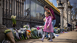 © Licensed to London News Pictures. 09/04/2021. London, UK. Josiah, 4 (L) and Nevaeh, 7 (C) lay flowers outside Buckingham Palace with their mother Tasha Pettman, following news of the death of Prince Philip. The Duke of Edinburgh Prince Philip, Queen Elizabeth II's husband, has died aged 99 Buckingham Palace has announced. Photo credit: Rob Pinney/LNP