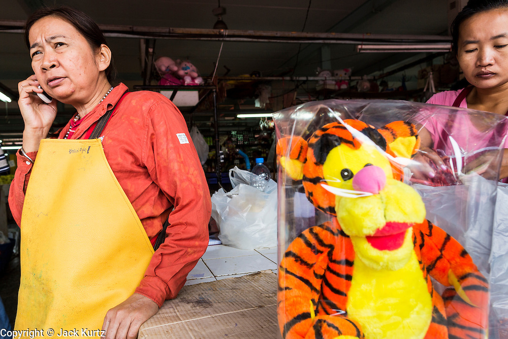 """24 AUGUST 2013 - BANGKOK, THAILAND: A woman selling tiger plush toys uses her mobile phone in Bangkok. Thailand entered a """"technical"""" recession this month after the economy shrank by 0.3% in the second quarter of the year. The 0.3% contraction in gross domestic product between April and June followed a previous fall of 1.7% during the first quarter of 2013. The contraction is being blamed on a drop in demand for exports, a drop in domestic demand and a loss of consumer confidence. At the same time, the value of the Thai Baht against the US Dollar has dropped significantly, from a high of about 28Baht to $1 in April to 32THB to 1USD in August.     PHOTO BY JACK KURTZ"""