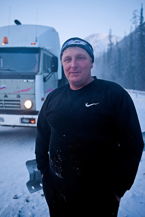 """Truck driver who is riding from Yakutsk to Magadan on the """"The Road of Bones"""" (M56 Kolyma Highway) during a break at Razluka brook. """"The Road of Bones"""" was constructed in the Stalin era of the USSR by Dalstroy construction directorate. The first stretch was built by the inmates of the Sevvostlag labor camp in 1932. The construction continued (by inmates of gulag camps) until 1953. The road is treated as a memorial, because the bones of the people who died while constructing it were laid beneath or around the road. The Verkhoyansk Range is a mountain range of eastern Siberia, spanning ca. 1000 km (600 m.), across the Sakha Republic..The world's lowest temperatures for inhabited places have been recorded in this region, and there is quite deep snow cover for most of the year. Verkhoyansk Range, Jakutien, Yakutia, Russian Federation, Russia, RUS, 18.01.2010"""