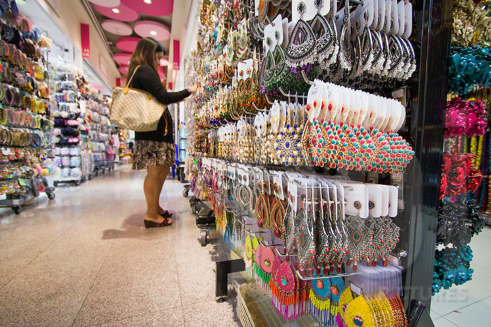 Young woman browses the accessory-lined wall of a shopping mall store, Bangkok, Thailand, Southeast Asia