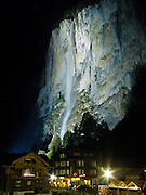 At night, floodlights brighten Staubbach Falls (Staubbachfall), highest waterfall in Switzerland, which plummets 1000 feet (300 meters). Lauterbrunnen town lights glow in the Berner Oberland, Switzerland, the Alps, Europe. The Bernese Highlands are the upper part of Bern Canton.