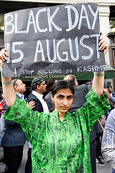 © Licensed to London News Pictures. 15/08/2019. LONDON, UK. A woman and a sign joins thousands of protesters, many waving Pakistani and Kashmiri flags, outside the Indian High Commission in Aldwych, on what they are calling Black Day, to stand in solidarity with the people of Kashmir.  Indian Prime Minister Narendra Modi delivered an Independence Day speech highlighting his decision to remove the special rights of Kashmir as an autonomous region.  Photo credit: Stephen Chung/LNP