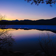 The sun sets over Chocorua Lake as the winter ice begins recedes