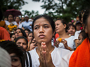 31 AUGUST 2014 - SARIKA, NAKHON NAYOK, THAILAND: A woman prays while a statue of Ganesh is submerged during the Ganesh Festival at Shri Utthayan Ganesha Temple in Sarika, Nakhon Nayok. Ganesh Chaturthi, also known as Vinayaka Chaturthi, is a Hindu festival dedicated to Lord Ganesh. It is a 10-day festival marking the birthday of Ganesh, who is widely worshiped for his auspicious beginnings. Ganesh is the patron of arts and sciences, the deity of intellect and wisdom -- identified by his elephant head. The holiday is celebrated for 10 days, in 2014, most Hindu temples will submerge their Ganesh shrines and deities on September 7. Wat Utthaya Ganesh in Nakhon Nayok province, is a Buddhist temple that venerates Ganesh, who is popular with Thai Buddhists. The temple draws both Buddhists and Hindus and celebrates the Ganesh holiday a week ahead of most other places.    PHOTO BY JACK KURTZ