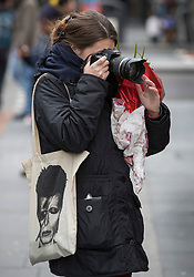 © Licensed to London News Pictures. 10/01/2017. London, UK. A fan carrying a bag with a photo of David Bowie on takes a photograph of a mural and shrine to the singer in Brixton on the first anniversary of his death. David Bowie was born in Brixton, south London. Photo credit: Peter Macdiarmid/LNP