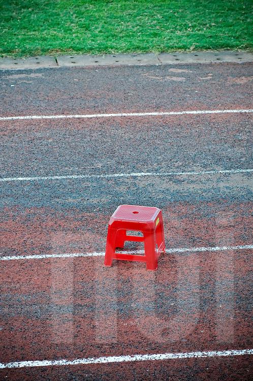 Tiny red plastic stool left on a stadium race track, Khanh Hoa area, Vietnam, Southeast Asia