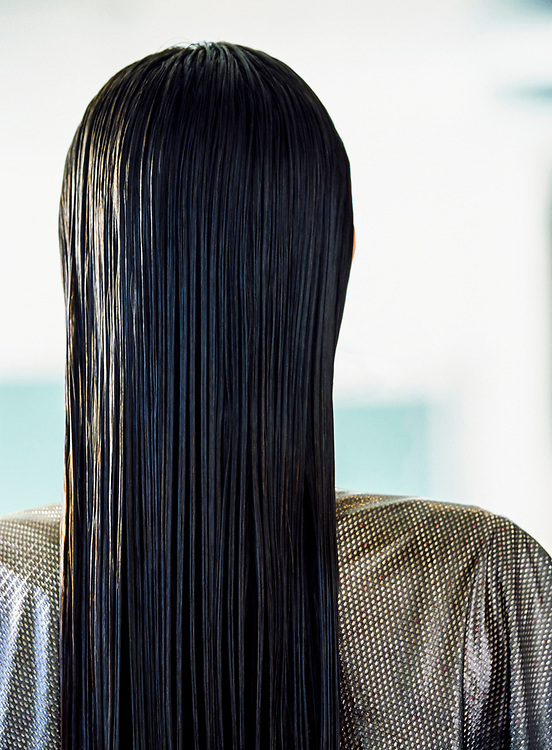 The back of a woman's head while sitting in a hair salon.