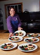 Saskia Esslinger serving plates of salmon burgers with apple cherry chutney for lunch at Winterlake Lodge, Finger Lake, Alaska.