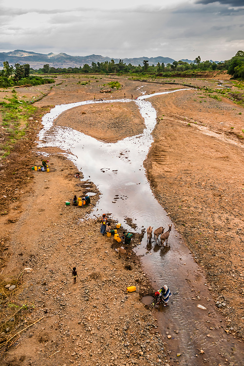 Konso tribe people filling water containers as donkeys drink from the Sagan River, near Konso, Ethiopia.
