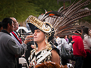 """03 DECEMBER 2011 - PHOENIX, AZ: An Aztec dancer marches in a procession to honor the Virgin of Guadalupe in Phoenix Saturday. The Phoenix diocese of the Roman Catholic Church held its Sixth Annual Honor Your Mother Day Saturday to honor the Virgin of Guadalupe. According to Mexican Catholic tradition, on December 9, 1531 Juan Diego, an indigenous peasant, had a vision of a young woman while he was on a hill in the Tepeyac desert, near Mexico City. The woman told him to build a church exactly on the spot where they were standing. He told the local bishop, who asked for some proof. He went back and had the vision again. He told the lady that the bishop wanted proof, and she said """"Bring the roses behind you."""" Turning to look, he found a rose bush growing behind him. He cut the roses, placed them in his poncho and returned to the bishop, saying he had brought proof. When he opened his poncho, instead of roses, there was an image of the young lady in the vision. The Virgin is now honored on Dec 12 in Catholic churches throughout Latin America and in Hispanic communitied in the US.  PHOTO BY JACK KURTZ"""