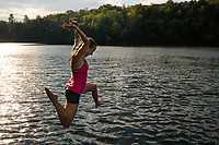 Katy Farber jumping into a beautiful, pristine Vermont lake during summer.  Greenwood Lake, Vermont