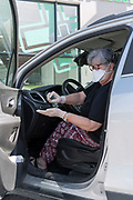 woman disinfecting her surgical gloves when getting in the car