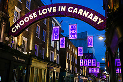 © Licensed to London News Pictures. 07/11/2020. London, UK. Carnaby Street Christmas lights in partnership with Choose Love. The installation will immerse Carnaby Street in pink neon lights, conveying the message of love, unity, and solidarity in these difficult times of the pandemic. The lights will be on display until January 5, 2021. Photo credit: Dinendra Haria/LNP