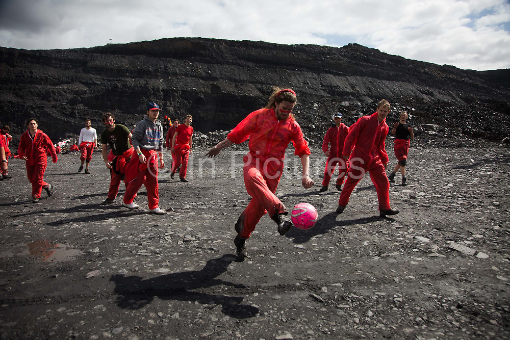 Hundreds of environmental activists stopping the open cast coal mine Ffos-y-Fran near Merthyr Tydfil, Wales from operating May 3rd 2016. A football match on the go in the middle of the mine. The activists from Reclaim the Power wants the mine shut down and a moratorium on all future open coal mining in Wales. The group Reclaim the Power had set up camp near by and had over three days prepared the action and up to 300 activists all dressed in red went into the mine in the early morning. The activist were plit in three groups and carried various props signifying the red line in the sand, initially drawn in Paris at the COP21. The mine is one of the largest open cast coal mines in the UK and is run by Miller Argent who have to date extracted 5million tons of coal. The activists entered the mine unchallenged by any security or police and the protest went on peacefully till mid afternoon with no arrests made.  Open coal mining is hugely damaging to the local environment and  contributing to global climate change.