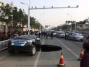 ZHENJIANG, CHINA - DECEMBER 12: (CHINA OUT) <br /> <br /> Car in Sink Hole<br /> <br /> A Ford sedan car halts on the verge of a 5 meters wide and 2 meters deep hole at Yunlianghe Road on December 12, 2014 in Zhenjiang, Jiangsu Province of China. A Ford sedan car halted on the verge of a hole at Yunlianghe Road after the road collapsed and formed a 5 meters wide and 2 meters deep hole abound 8 o'clock on Friday morning. The road is just opened for two years and the reason is still under investigation.<br /> ©Exclusivepix Media