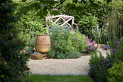 Wooden bench in gravel area. Empty terracotta urn with nigella, alliums and Geranium plamatum