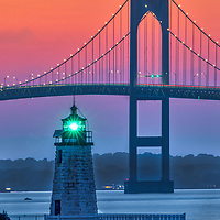 Goat Island Lighthouse also known as Newport Harbor Light in Newport , Rhode Island. This historic Rhode Island lighthouse with its iconic white stone tower and a fixed green light is located in Narragansett Bay guiding the way into Newport Harbor. In the background towers the famous Newport Bridge.<br /> <br /> Newport Harbor Light photography photos are available as museum quality photo, canvas, acrylic, wood or metal prints. Wall art prints may be framed and matted to the individual liking and New England interior design projects decoration needs.<br /> <br /> Good light and happy photo making!<br /> <br /> My best,<br /> <br /> Juergen