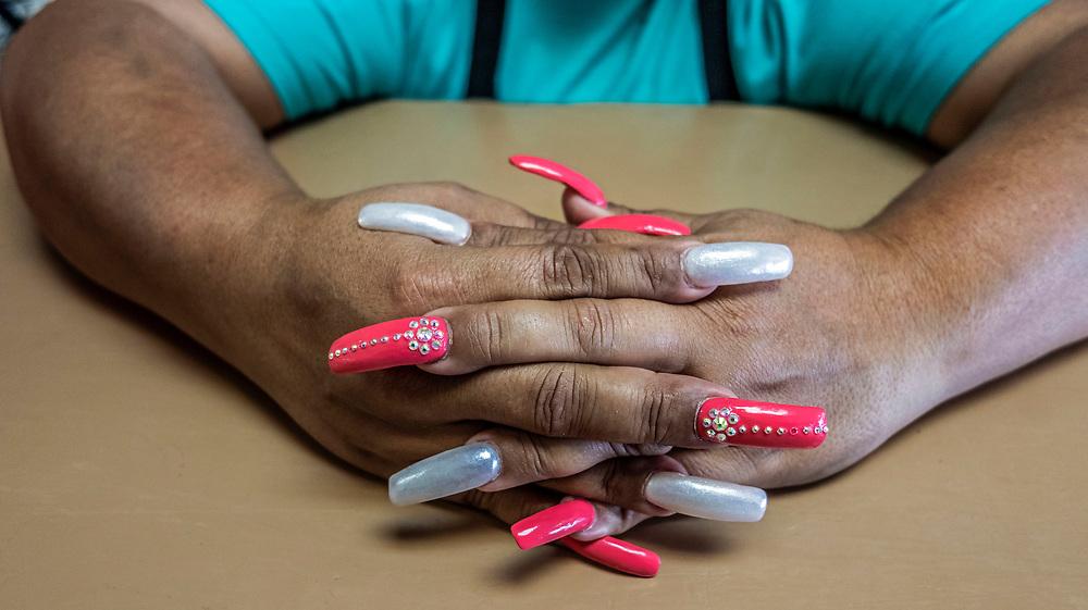 Female with colourful acrylic false nails.