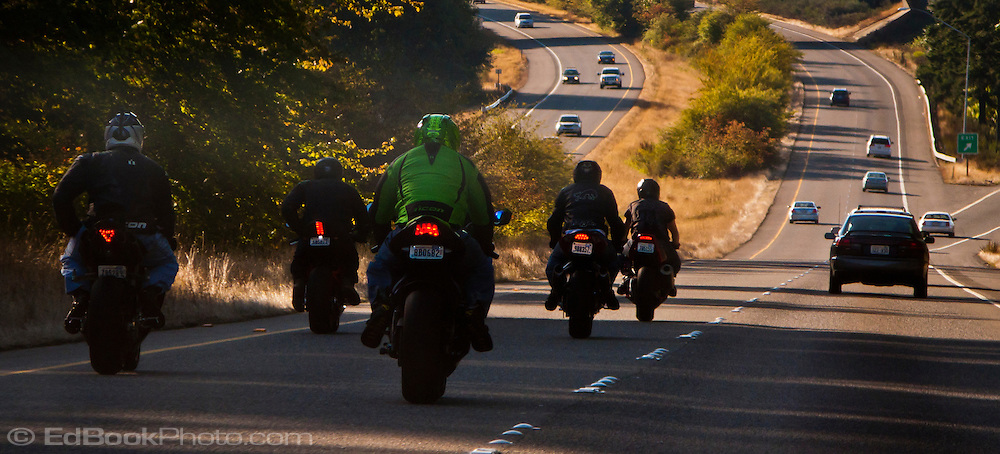 a group or motorcyclists riding sport bikes cruise down the freeway in a close pack in the fast lane. Washington State Route 17 neaing Gig Harbor on the Kitsap Peninsula in Puget Sound, Washington state, USA
