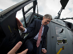© London News Pictures. 11/07/2012. Farnborough, UK. Defence Secretary Philip Hammond  getting out of a wildcat after officially receiving first Wildcat helicopters from AgustaWestland on behalf of the armed forces on day three of the Farnborough International Airshow, in Farnborough, Hampshire, UK on July 9, 2012. FIA is a seven-day international trade fair for the aerospace industry which is held every two years at Farnborough Airport . Photo credit: Ben Cawthra/LNP.