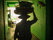 24 FEBRUARY 2015 - PHNOM PENH, CAMBODIA: A food vendor walks through a hallway in the White Building. The White Building, the first modern apartment building in Phnom Penh, originally had 468 apartments, and was opened the early 1960s. The project was overseen by Vann Molyvann, the first Cambodian architect educated in France. The building was abandoned during the Khmer Rouge occupation. After the Khmer Rouge were expelled from Phnom Penh in 1979, artists and dancers moved into the White Building. Now about 2,500 people, mostly urban and working poor, live in the building. Ownership of the building is in dispute. No single entity owns the building, some units are owned by their occupants, others units are owned by companies who lease out apartments. Many of the original apartments have been subdivided since the building opened and serve as homes to two or three families. The building has not been renovated since the early 1970s and is in disrepair. Phnom Penh officials have tried to evict the tenants and demolish the building but residents refuse to move out.   PHOTO BY JACK KURTZ