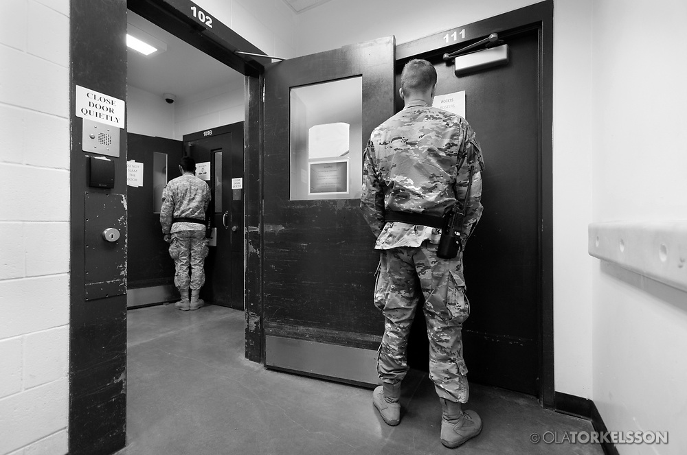 """Military guards at the prison camp at Guantanamo, Cuba, Jan 28 2017, guards an entrance to a cell block.<br /> The guards turn away their faces so you cannot identify them. It is standard operation procedure when pictures are made. When you work as a journalist at the Guantanamo you work under military censorship and all your material is checked every day and approved for publication.<br /> The prison camp on the Guantánamo naval base was the creation of President George W. Bush. The prison camp was considered an important part of the US war on terrorism. Over the years, 779 people have been brought to the camp. 41 people are still detained. Of them, 26 people count as """"forever prisoners"""", indefinite detainees under the Law of War. Two prisoners have been in the camp since it was opened in January 2002. The last prisoner taken to the camp came in March 2008. The so-called war on Terror and the Guantanamo prison camp have been heavily criticized for violation of human rights regarding torture and habeas corpus.<br /> It is unclear what US President Donald Trump wants to do with the camp, but during the election campaign he said that he would fill Guantánamo Bay with """"bad dudes"""". Photo by Ola Torkelsson<br /> Copyright Ola Torkelsson ©"""