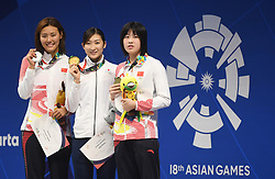 JAKARTA, Aug. 24, 2018  Gold medalist Ikee Rikako (C) of Japan, silver medalist Liu Xiang (L) of China and bronze medalist Wu Qingfeng of China attend the awardng ceremony after women's 50m freestyle final of swimming at the 18th Asian Games in Jakarta, Indonesia, Aug. 24, 2018. (Credit Image: © Pan Yulong/Xinhua via ZUMA Wire)