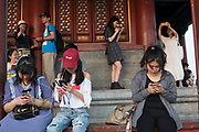 Beijing Jingshan Park, at temple, women and girls watching mobile telephone. China