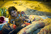 Radhika, 15 plays with her sisters beneath a quilt under the busy IIT flyover where the family live, New Delhi, India.