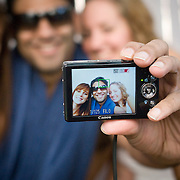 An Indian guy and two foreign girls take  a picture of themselves together at the Aqua pool club of the Park Hotel in New Delhi.