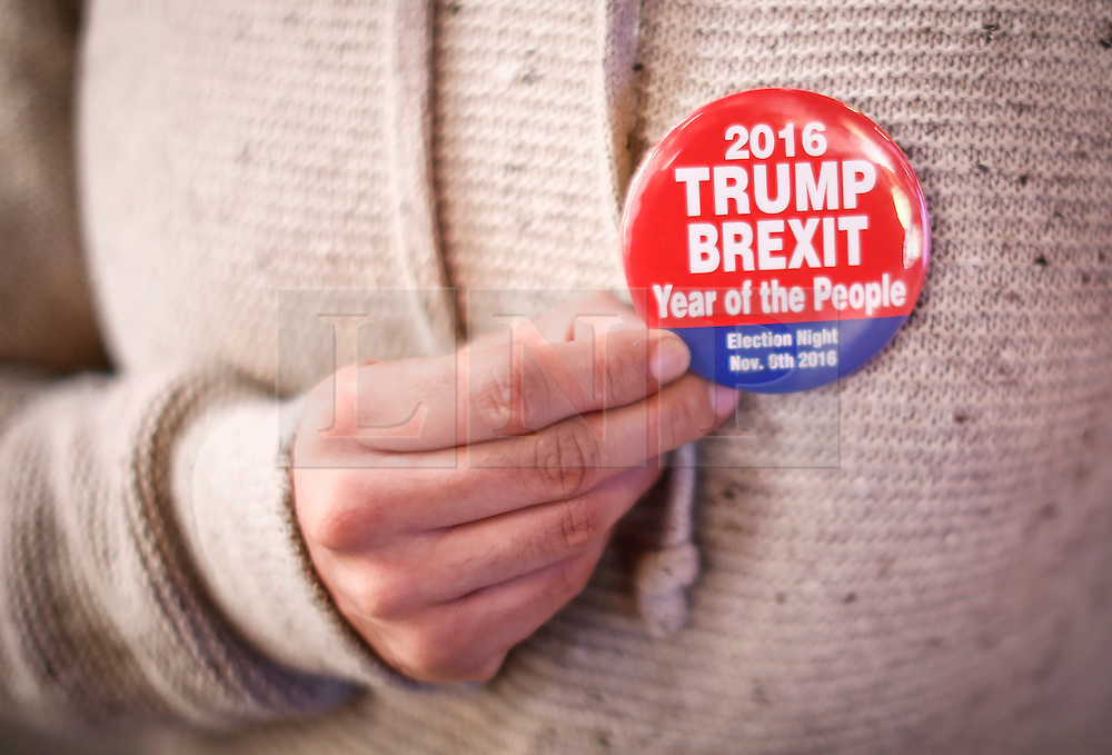 """© Licensed to London News Pictures. 09/11/2016. New York City, A woman holds a badge reading """"2016 TRUMP, BREXIT, Year of the People"""" while watching election coverage in Times Square, New York City, on Wednesday, 9 November. Photo credit: Tolga Akmen/LNP"""