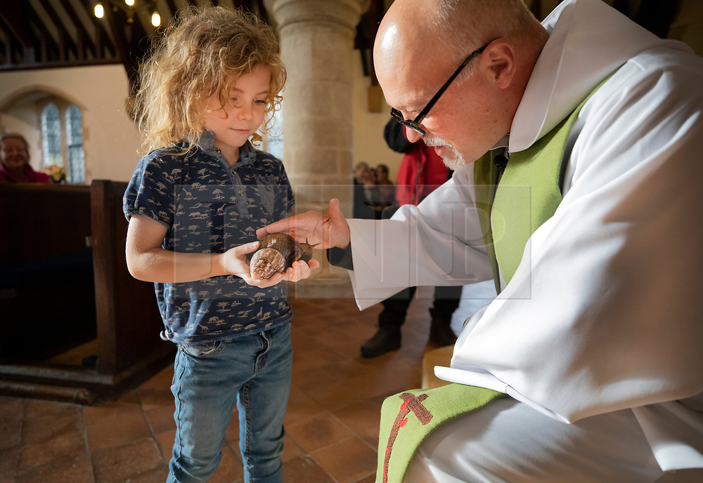 © Licensed to London News Pictures. 06/10/2019. Selsey, UK. Father Andy Wilkes blesses 9 year old Lennon's Giant African Land Snail named Alan during the annual Service of Blessing of Animals at St Peter's Church in Selsey, West Sussex. Parishioners bring their pets to the church for the annual service after earlier attending a Harvest Festival celebration. Photo credit: Peter Macdiarmid/LNP
