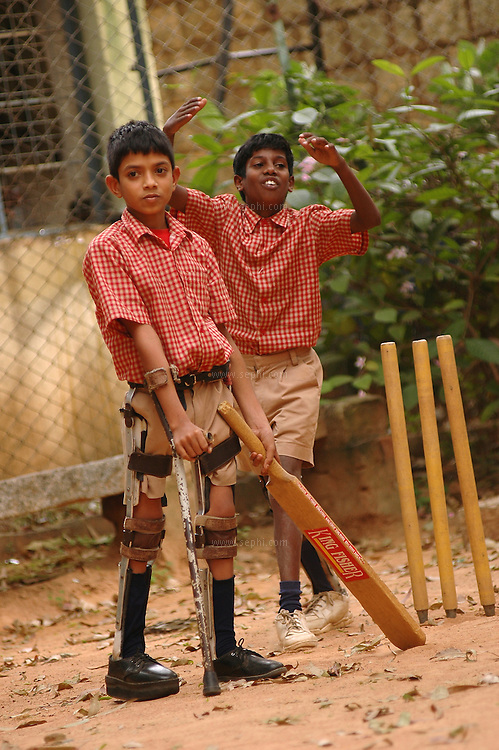 At the end of the school day, Sultan (11) plays a game of cricket with his friends at the schools playground. He suffers from polio with PPRP (postal resistrial paralysis)