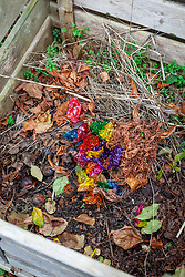 Putting Quality Street sweet wrappers on the compost heap