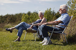 A couple sitting on an embankment in sunchairs enjoying the sunshine,