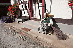 Typical harzer witch doll in front of old timber framed buildings