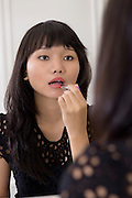 Young Vietnamese lady putting on makeup for a night out.
