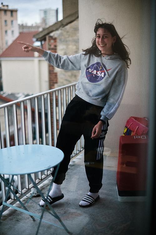 La photographe Rebecca Toakian prenant la pose sur son balcon. Maisons-Alfort, France. 16 fevrier 2020.