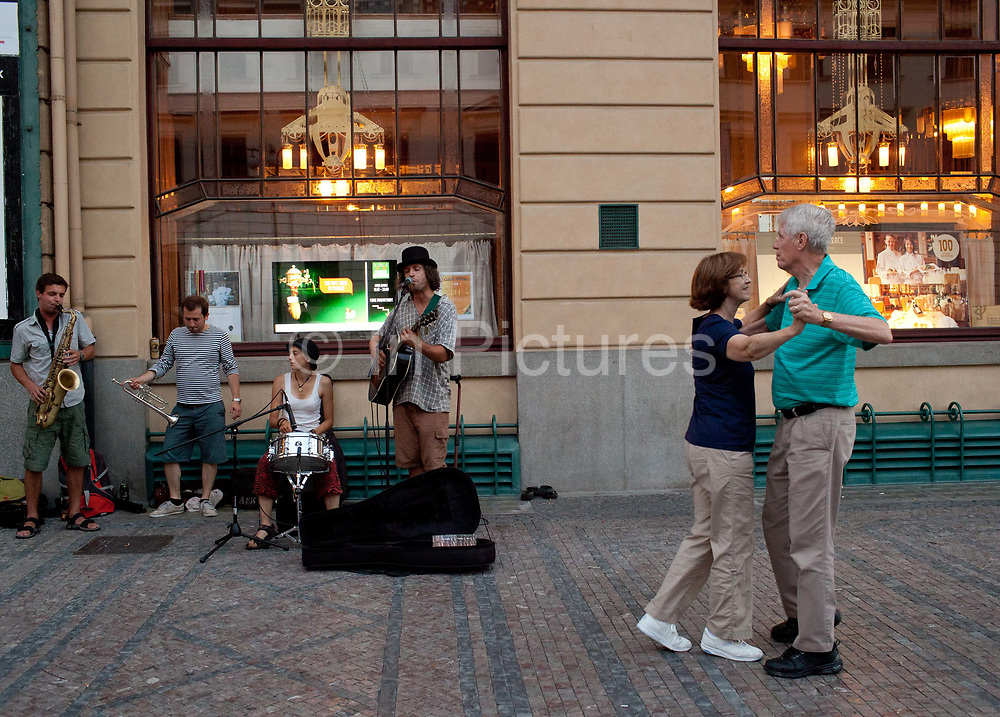 Elderley couple dancing in the street with a band playing in the background, outside the Municpial house; Prague, Czech Republic.