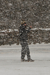 © Licensed to London News Pictures. 06/04/2021. Llanberis, Conwy, Wales, UK. A man takes photos in a blizzard at Pen-Y-Pass as snow and hail hit Snowdonia National Park, in Conwy, Wales, UK. Photo credit: Graham M. Lawrence/LNP
