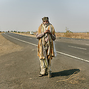 """On a spiritual quest.<br /> I saw him at the last second and had to reverse the car to get back to him. He was covered in blankets. Two different shoes. No bag, no water. """"My name is Binod Yasin, I am walking ahead.""""<br /> Maharashtra province."""
