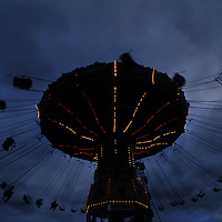 Australia, New South Wales, Minchinburg, Carnival ride under cloud-filled sky on summer evening